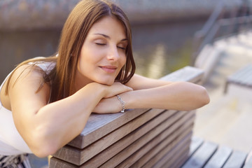 frau sitzt draußen auf einer bank und träumt