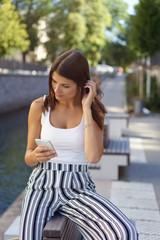 frau sitzt in einem park in der stadt und schaut auf ihr mobiltelefon