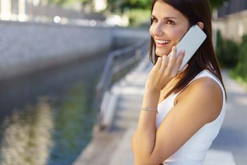 lachende frau telefoniert in der stadt