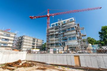 Baustelle mit Baukran und Fundament eines Neubaus und Wohnungen im Hintergrund