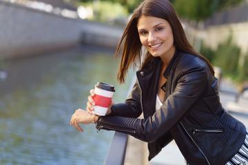 entspannte frau mit einem becher kaffee in der stadt