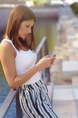 frau steht draußen und schaut mit ernstem gesicht auf ihr mobiltelefon