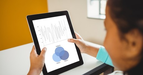 Businesswoman analyzing graphs on tablet PC