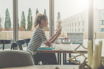 Side view,young businesswoman in striped T-shirt sits in cafe at wooden table in front of window and uses smartphone.