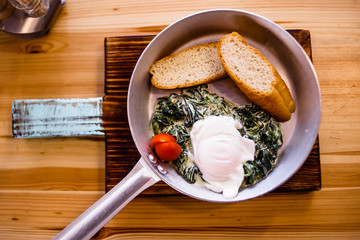 Breakfast at the frying pan - fried spinach, egg poached, bread, tomato