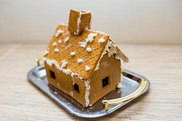 Gingerbread house stands on a tray on a table