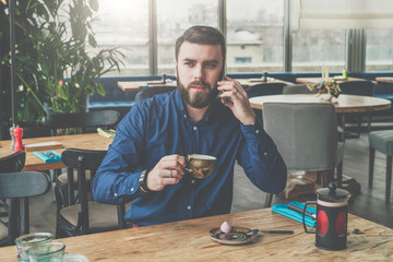 Young bearded businessman in blue shirt is sitting at wooden table in restaurant,talking on phone and drinking tea