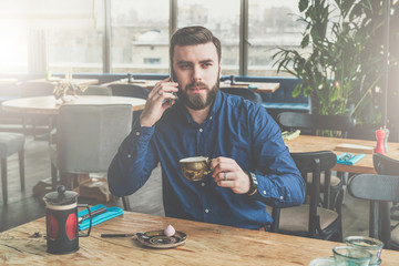 Young bearded attractive businessman in blue shirt is sitting at wooden table in restaurant, talking on phone