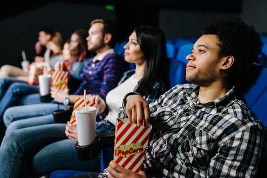 Mixed race group of people watching a movie