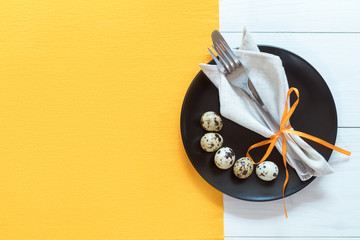 Easter table setting with cutlery. Rustic orange table cloth on white wood background. Holidays background with copy space.
