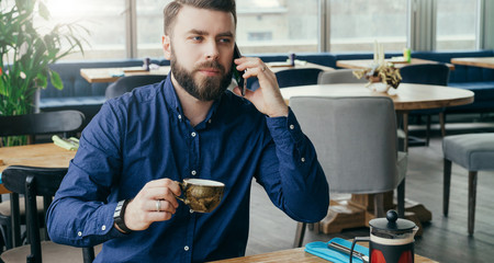 Young bearded attractive businessman sitting at wooden table in restaurant, talking on phone and drinking tea.