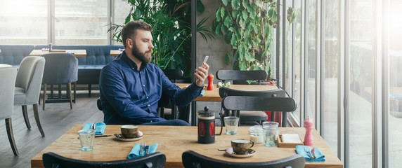 Bearded attractive businessman in blue shirt is sitting at wooden table near window in restaurant and holding smartphone