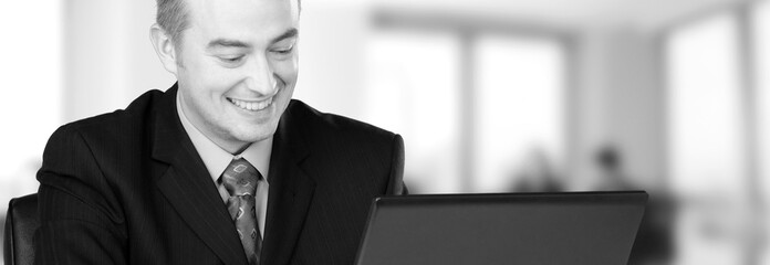 Young happy businessman working in his office in black and white
