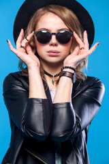 Fashion hipster woman posing on blue background. Black hat, leather jacket, blond curly hair, bright red lips, sunglasses.Trendy fashion summer style.