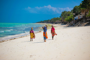 Three women walking on the beach in Jambiani, Zanzibar island, Tanzania