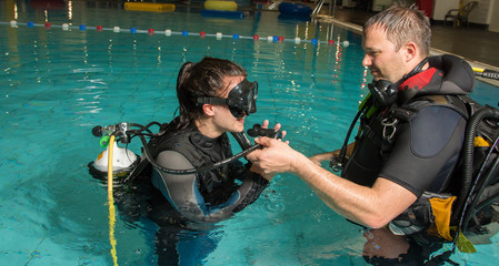 teen girl gets scuba diving lesson from an instructor in a swimming pool scuba diving course
