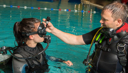 teen girl gets scuba diving lesson from an instructor in a swimming pool scuba diving course Wall mural