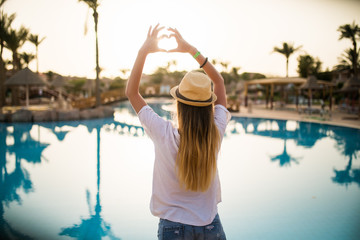 Woman make heart with hands on sun near pool on summer vocation.