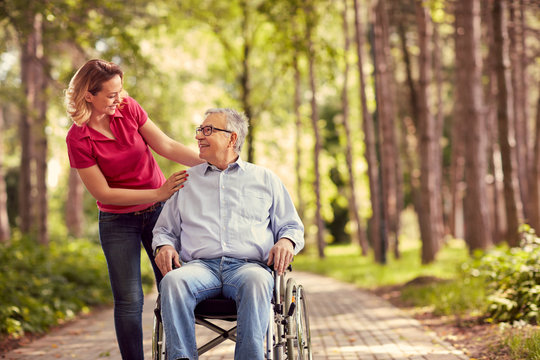 smiling woman with her disabled father in wheelchair.