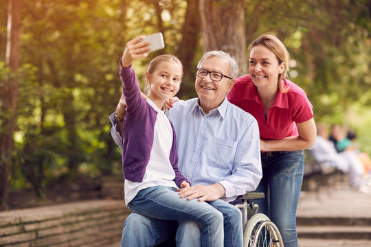 granddaughter using phone for selfie with her disabled father in wheelchair and mother.