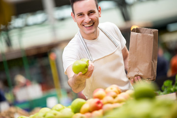 happy salesman holding apple at a market stall..