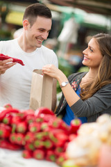 Couple choosing red pepper in grocery store.