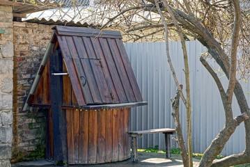 Коричневый деревянный колодец во дворе