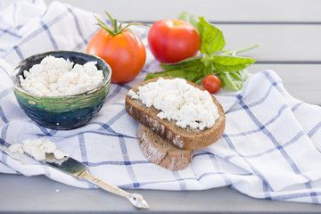 Organic Farming Cottage cheese in a green bowl, slice of whole wheat bread with Homemade Ricotta cheese served with tomatoes and basil on wooden board  on linen fabric. Healthy food concept