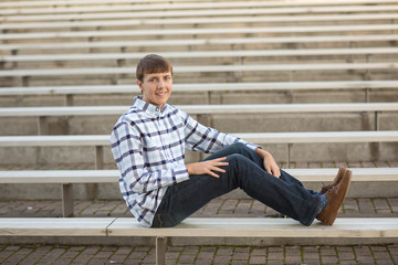 high school male sitting on bleachers