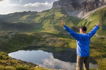 Hiker standing with raised hands near the beautiful mountain lake at sunset