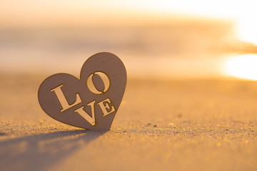 Wooden heart with inscription Love on seaside at dawn