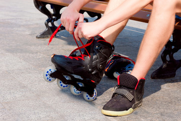 Sporty guy sitting on the bench and putting on his roller skates
