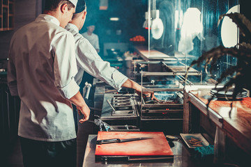 Food concept. Two chefs in white uniform monitor the degree of roasting meat with hand in interior of modern restaurant kitchen. Preparing traditional beef steak on barbecue oven from stainless steel