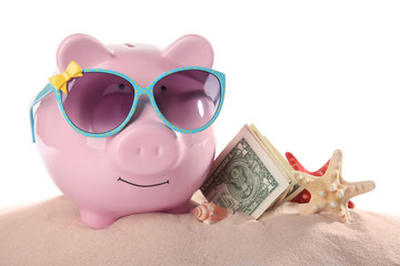 Vacation budget concept. Piggy bank with money and seashells on sand against white background