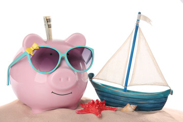 Vacation budget concept. Piggy bank with sunglasses and toy sailboat on sand against white background