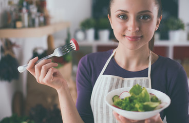 Poster Bar Young woman eating fresh salad in modern kitchen
