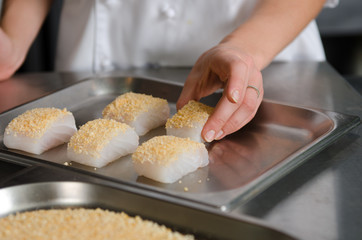 Fresh fish fillet cube covered in breadcrumbs, being placed onto a metal baking tray.