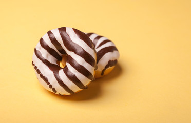 two striped chocolate donuts isolated on yellow background
