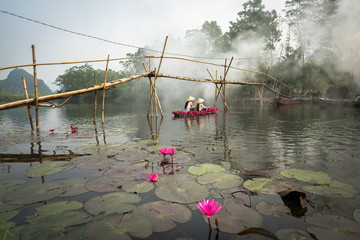 River scene with smoke, a boat carrying girls wearing traditional dress Ao Dai, conical hat, and...