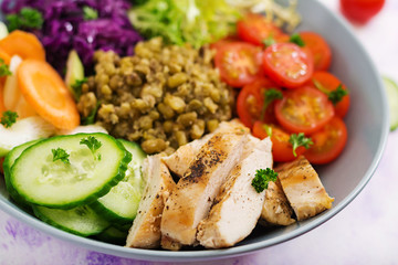 Healthy salad with chicken, tomatoes,  cucumber, lettuce, carrot, celery, red cabbage and  mung bean on light  background. Proper nutrition. Dietary menu.