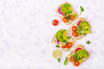Vegan sandwiches with avocado, watermelon radish and tomatoes on a white background. Flat lay. Top view