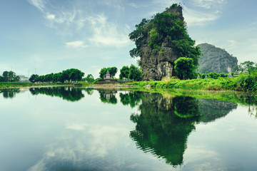 Amazing natural karst tower reflected in water. Toned image