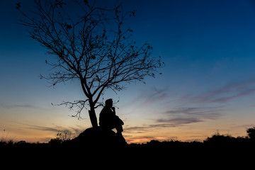 silhouettes Man sitting under the tree