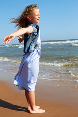 Happy child stands on the shore of the ocean with arms outstretched.