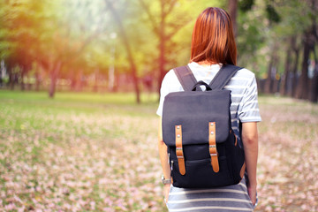 Hipster young girl with backpack enjoying sunset .