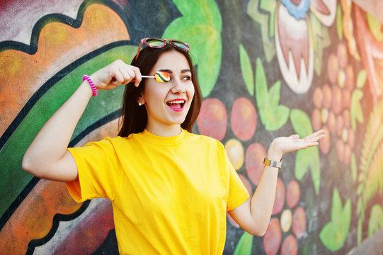 Beautiful teenage with lollipop, wear yellow t-shirt near graffiti wall.