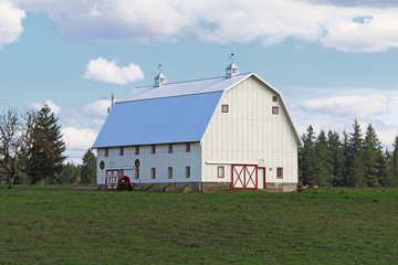 Large White Barn with Red Trim, Vivid Green Grass/Blue Sky, Bright White Clouds, Daytime - Center frame, three-quarter viewpoint (HDR Image)