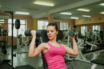Beautiful girl exercising in fitness club with dumbbells.
