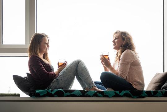 Women having tea at home on window ledge bed
