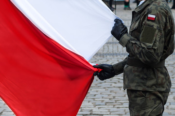 Polish national flag held by a soldier during a ceremony